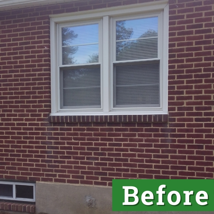 white double pane windows and a small basement window on a brick house