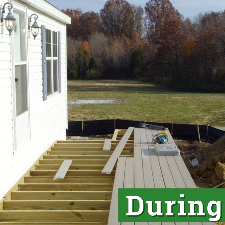 an unfinished deck attached to a white house