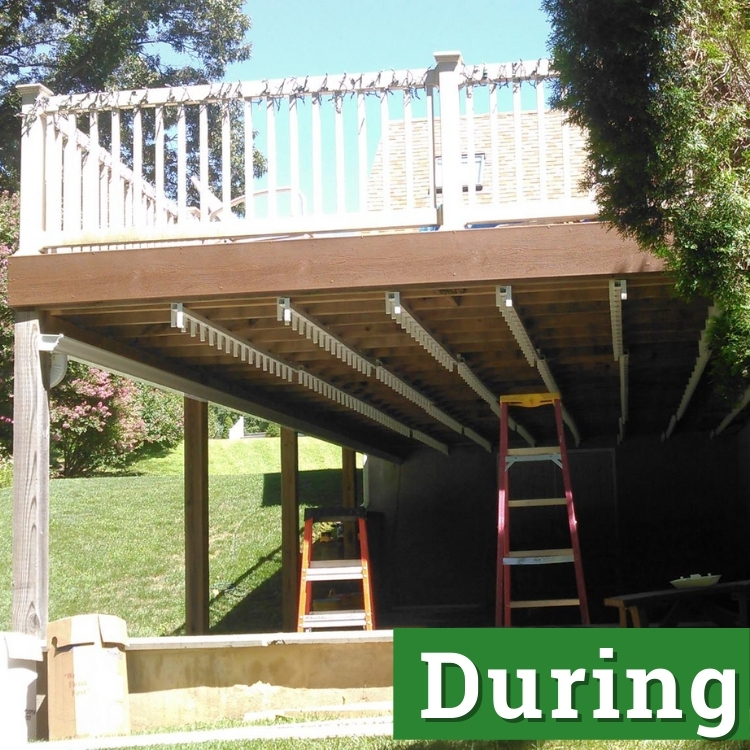 two ladders stand under a second story deck in the process of being built