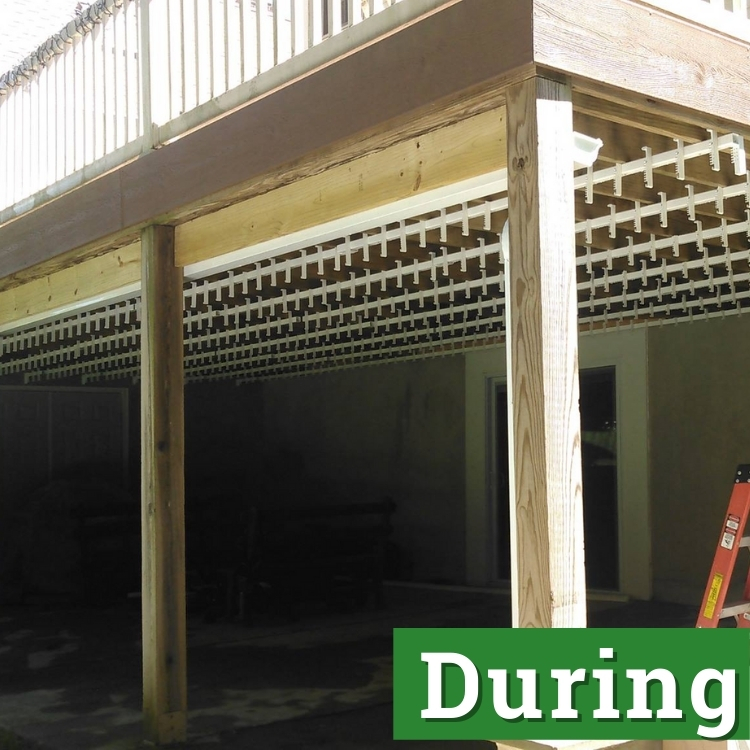 wooden beams and white deck supports under a second story deck in the process of being built
