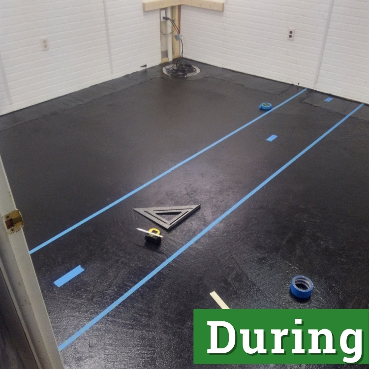 two lines of blue tape map out an area on a black floor