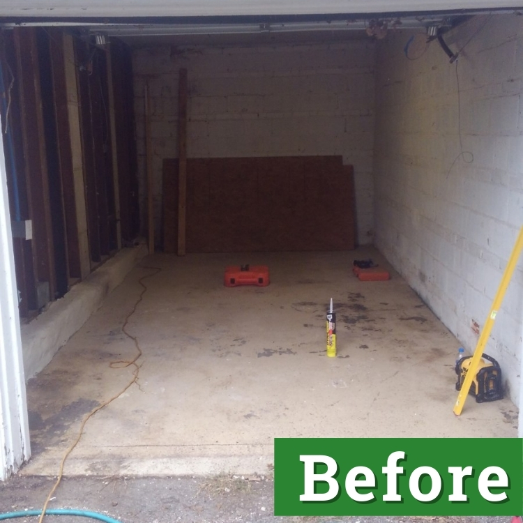 caulk and a tool box rest on the cement floor of a garage that is about to be converted into living space