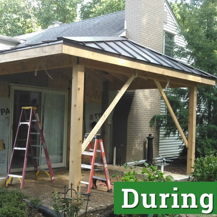 two ladders stand under new framing for an outdoor patio with partial enclosure roof