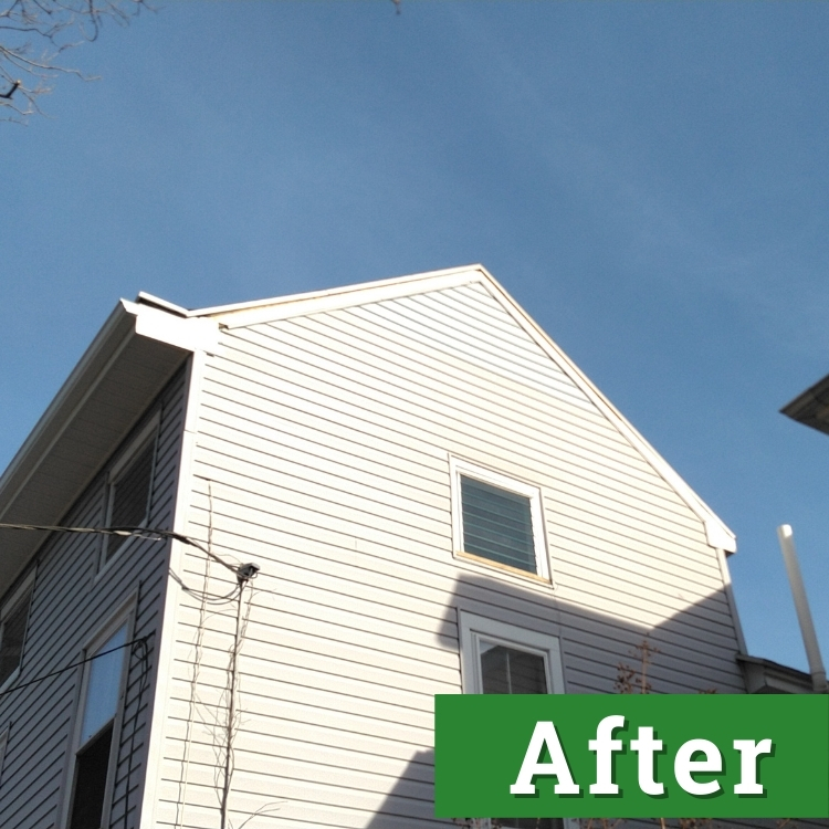 new siding near the roof of a light gray house