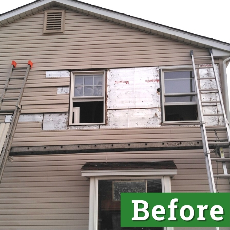 two ladders lean against storm-damaged siding of a brown house