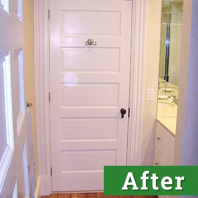a newly installed white bathroom door and cabinetry
