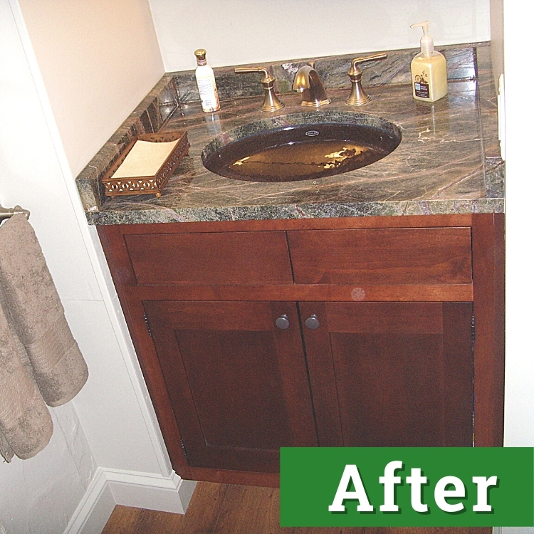 a mahogany bathroom cabinet with a black marble countertop