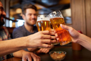 men clinking glasses of beer