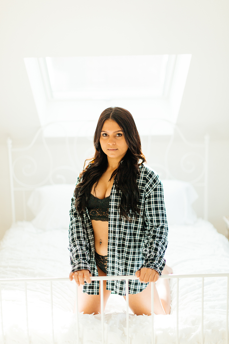 A beautiful young German woman poses on a white bed wearing a black bra and underwear with a plaid button up shirt for a Kaiserslautern studio boudoir shoot in Kindsbach, Germany