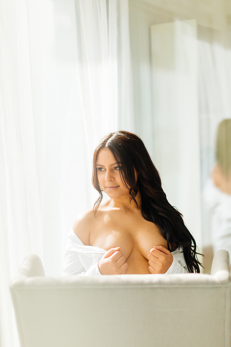 A beautiful young German woman poses on a chair in front of a window wearing black underwear and a white button up shirt for a Kaiserslautern studio boudoir shoot in Kindsbach, Germany