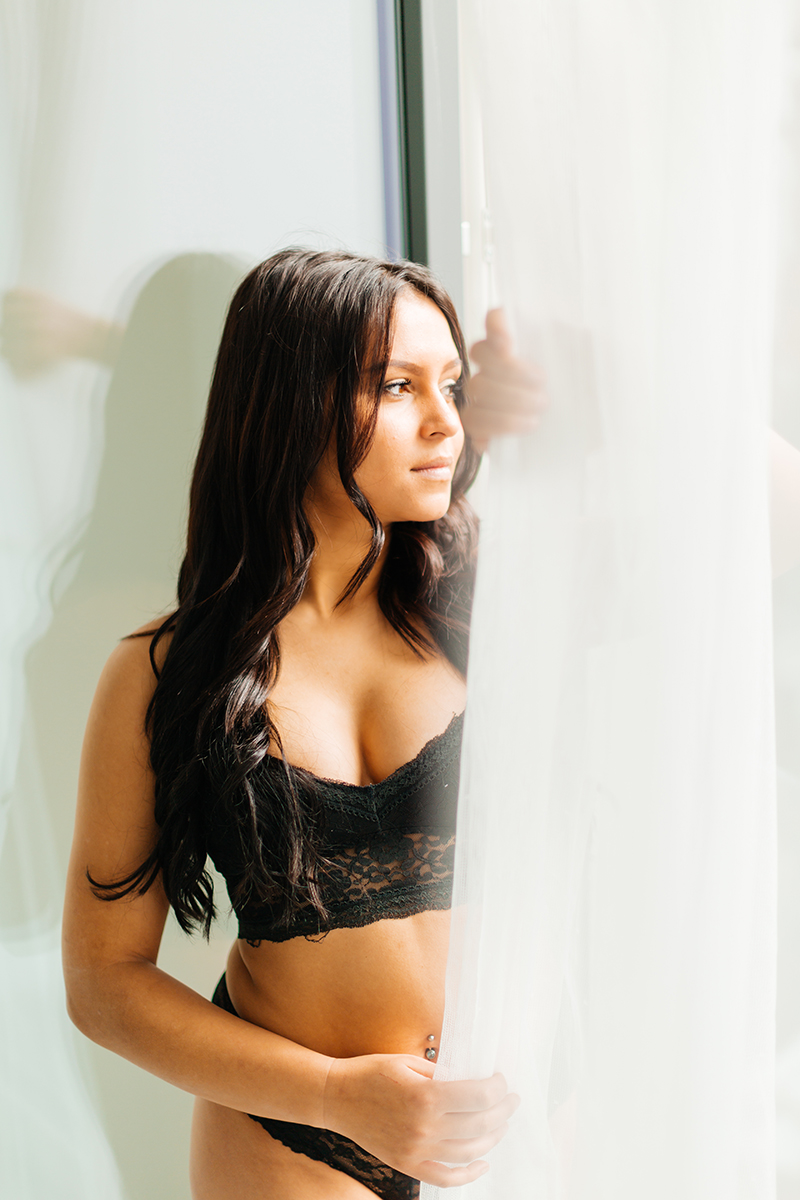 A beautiful young German woman poses in front of a window with sheer curtains wearing a black bra and underwear for a Kaiserslautern studio boudoir shoot in Kindsbach, Germany