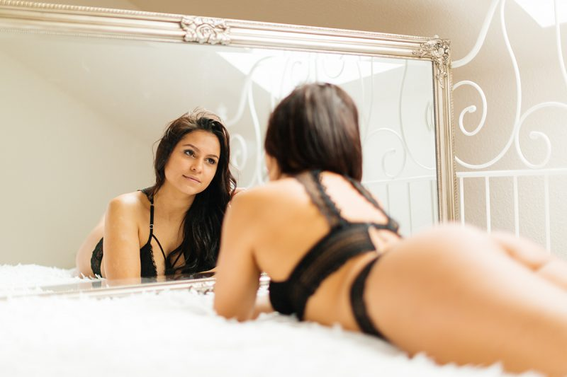 A beautiful young German woman poses on a white bed in front of a mirror wearing a black bra and underwear for a Kaiserslautern studio boudoir shoot in Kindsbach, Germany
