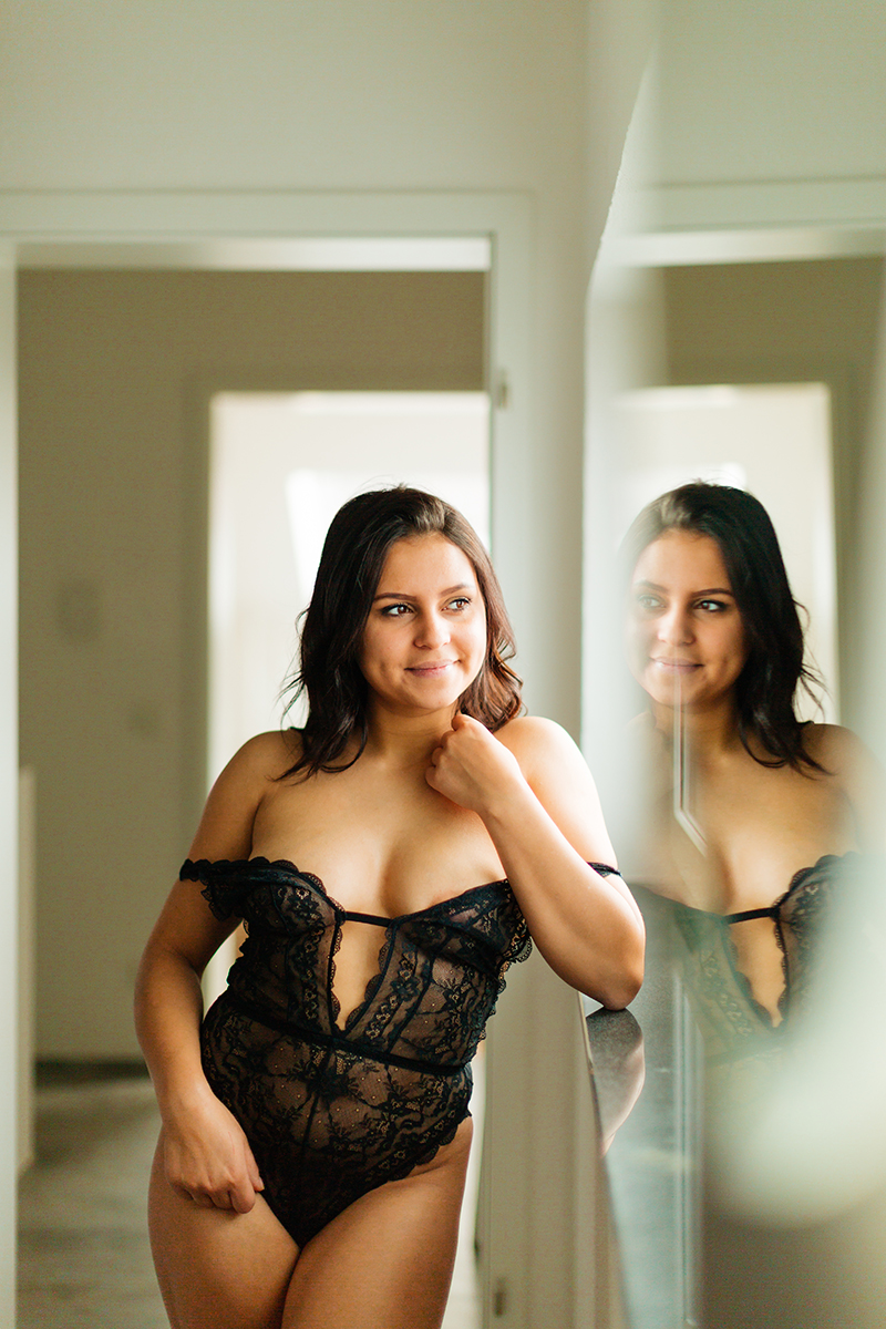 A beautiful young German woman poses in a bathroom wearing black lingerie in front of a mirrr for a Kaiserslautern studio boudoir shoot in Kindsbach, Germany