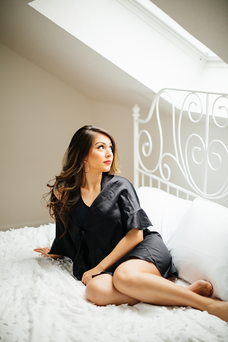 A beautiful brunette woman posing in a black bra and black underwear with a black robe on a white bed during a Kindsbach boudoir studio photography session near Kaiserslautern, Germany