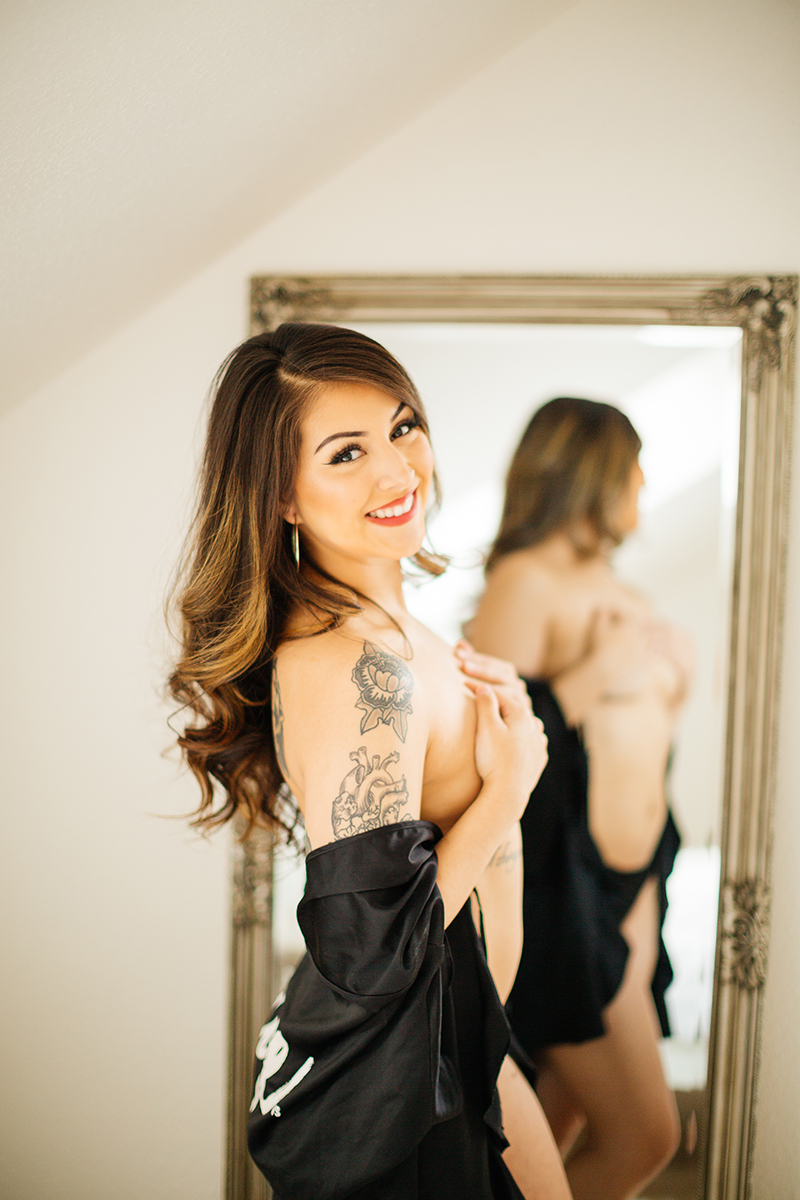 A beautiful brunette woman posing topless in black underwear with a black robe in front of a mirror during a Kindsbach boudoir studio photography session near Kaiserslautern, Germany