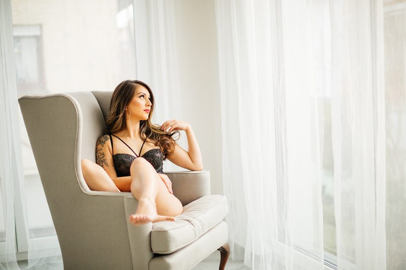A beautiful brunette woman posing in black lingerie on a gray chair in front of white curtains during a Kindsbach boudoir studio photography session near Kaiserslautern, Germany