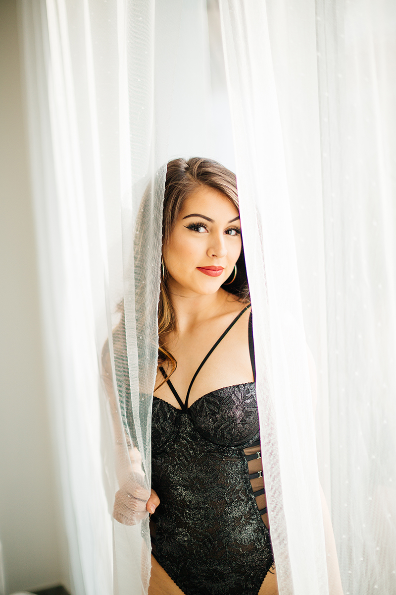 A beautiful brunette woman posing in black lingerie next to a window with sheer curtains during a Kindsbach boudoir studio photography session near Kaiserslautern, Germany