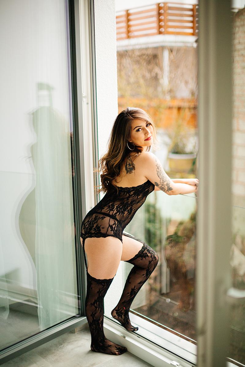 A beautiful brunette woman posing in black lingerie in an open window during a Kindsbach boudoir studio photography session near Kaiserslautern, Germany
