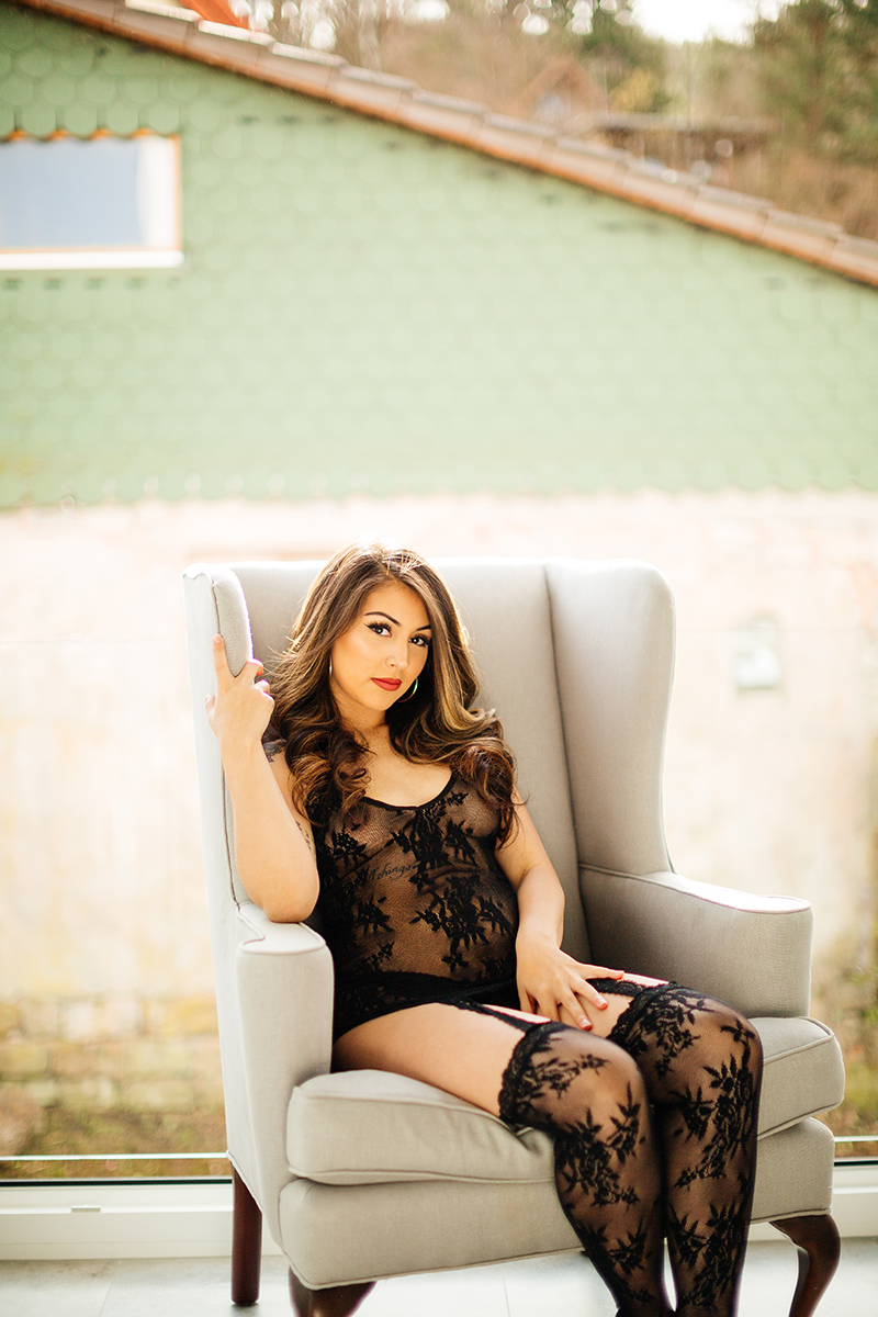 A beautiful brunette woman posing in black lingerie sitting in a gray chair in front of an open window during a Kindsbach boudoir studio photography session near Kaiserslautern, Germany