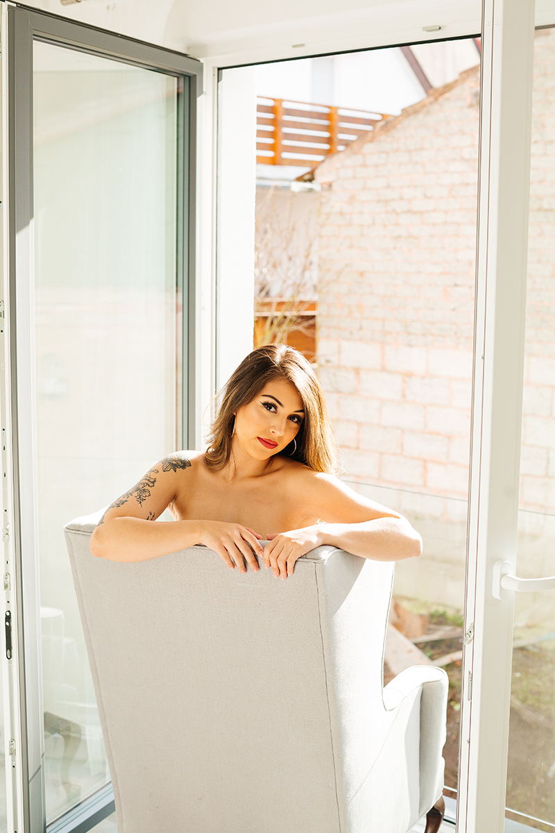 A beautiful brunette woman posing topless sitting on a gray chair in front of an open window during a Kindsbach boudoir studio photography session near Kaiserslautern, Germany