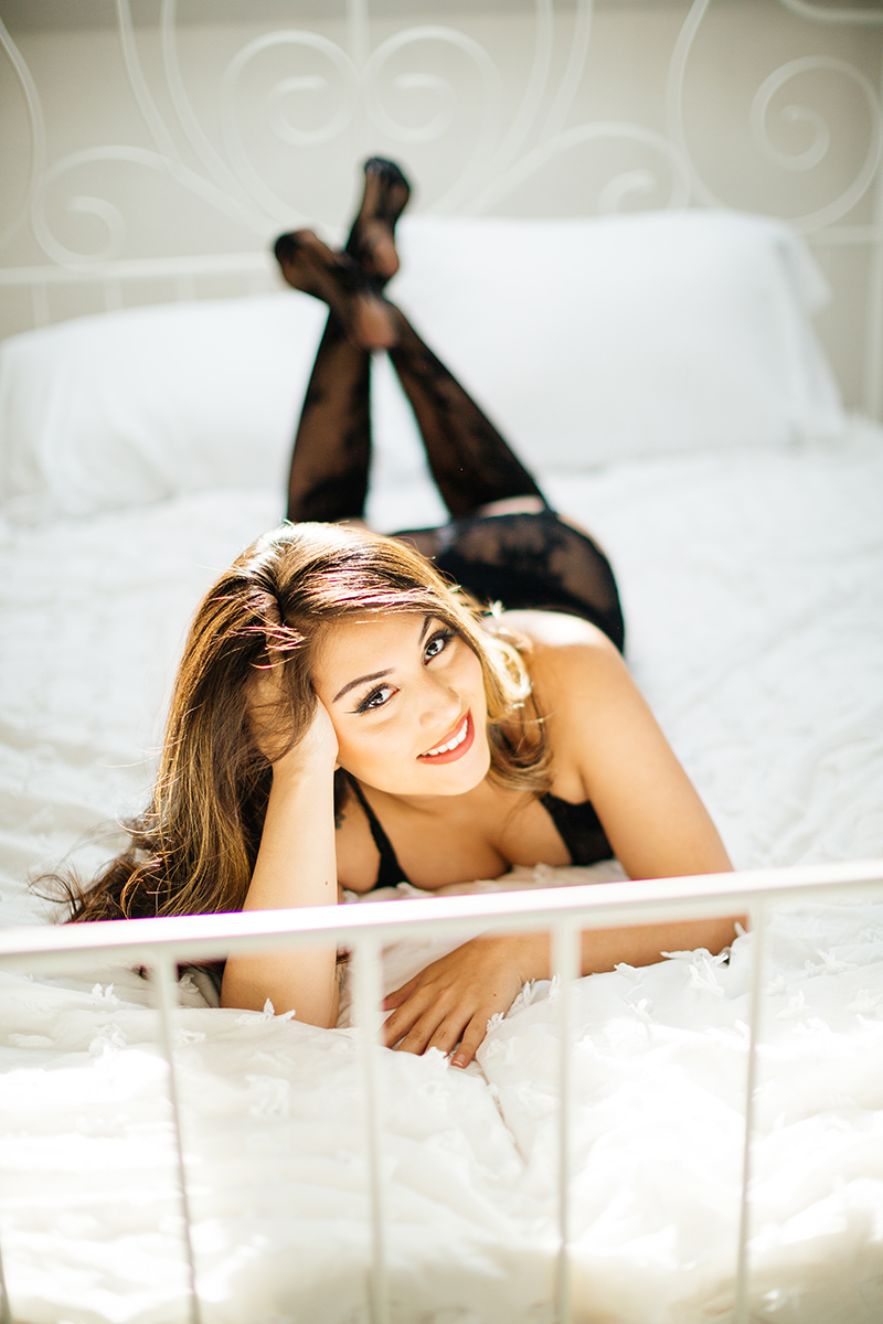A beautiful brunette woman posing in black lingerie and black stockings on a white bed during a Kindsbach boudoir studio photography session near Kaiserslautern, Germany