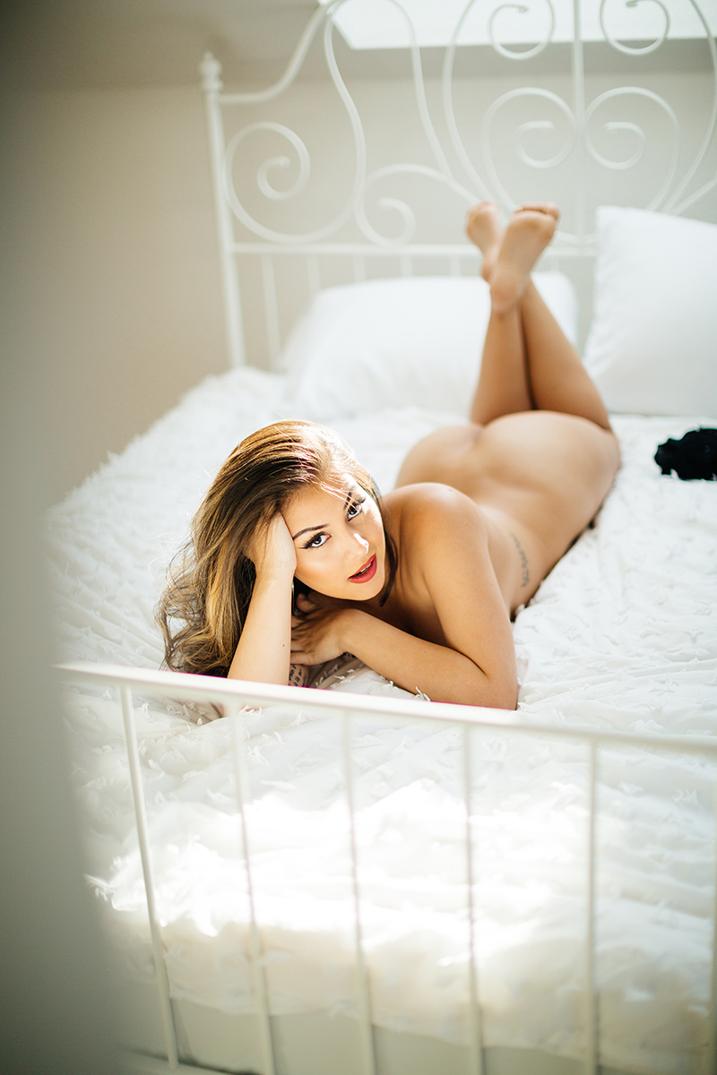 A beautiful brunette woman posing nude on a white bed during a Kindsbach boudoir studio photography session near Kaiserslautern, Germany