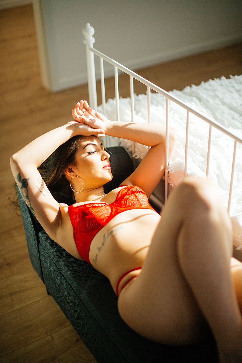A beautiful brunette woman posing in a red bra and underwear set on a gray lounge chair during a Kindsbach boudoir studio photography session near Kaiserslautern, Germany