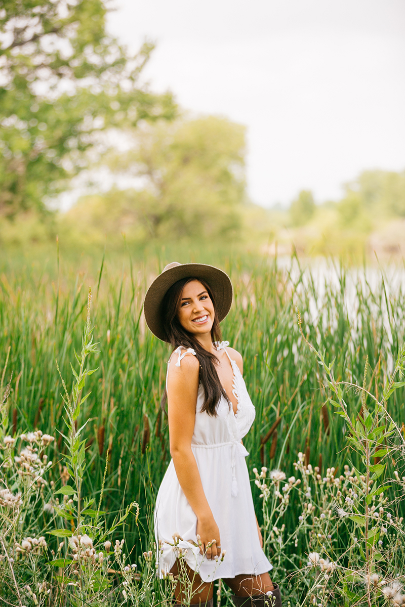 A beautiful young brunette poses in front of tall grass at a lake wearing a white dress and a straw hat for a St Vrain fashion photography session near Denver, Colorado