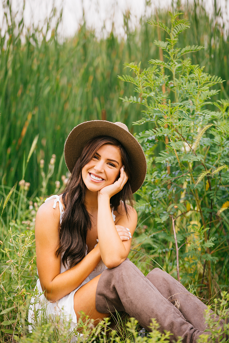 A beautiful young brunette poses sitting in front of tall grass at a lake wearing a white dress, tan boots and a straw hat for a St Vrain fashion photography session near Denver, Colorado
