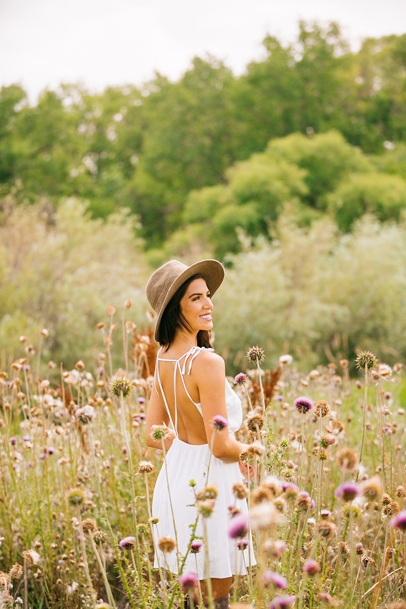 A beautiful young brunette poses in a field of wild flowers wearing a white dress and a straw hat for a St Vrain fashion photography session near Denver, Colorado