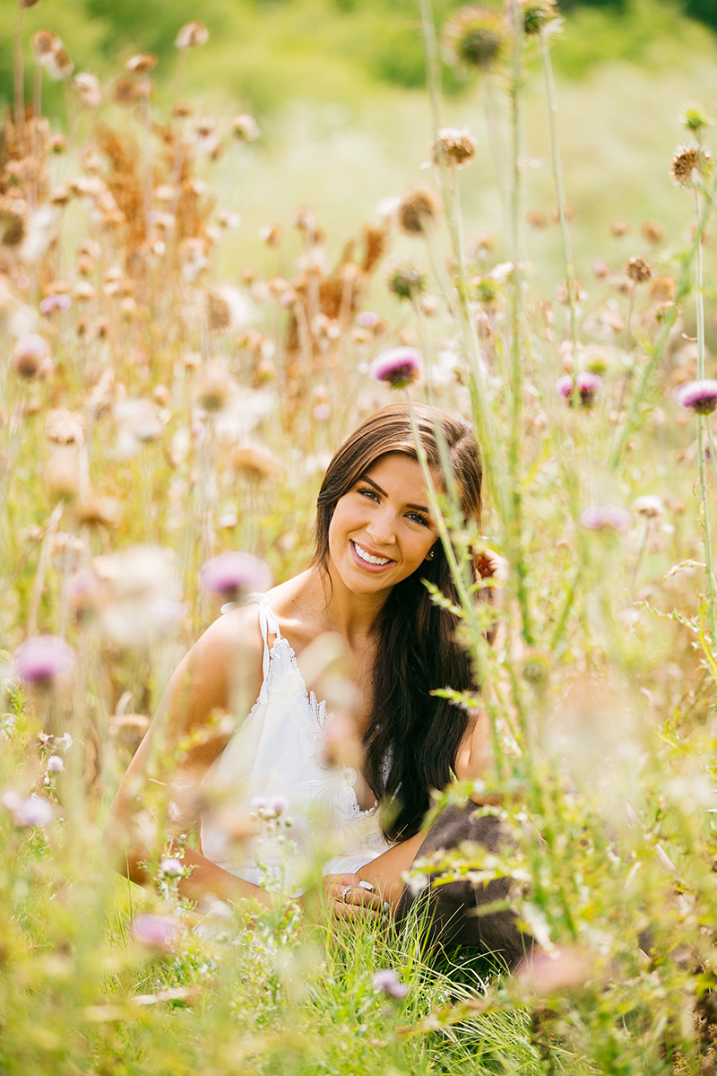 A beautiful young brunette poses sitting in a field of wild flowers wearing a white dress for a St Vrain fashion photography session near Denver, Colorado