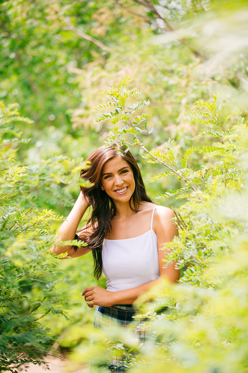 A beautiful young brunette poses in a lush green path surrounded by bushes wearing a white top and a plaid skirt for a St Vrain fashion photography session near Denver, Colorado