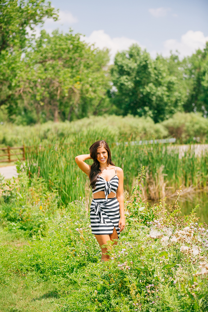 A beautiful young brunette poses in a lush green field wearing a striped top and skirt for a St Vrain fashion photography session near Denver, Colorado