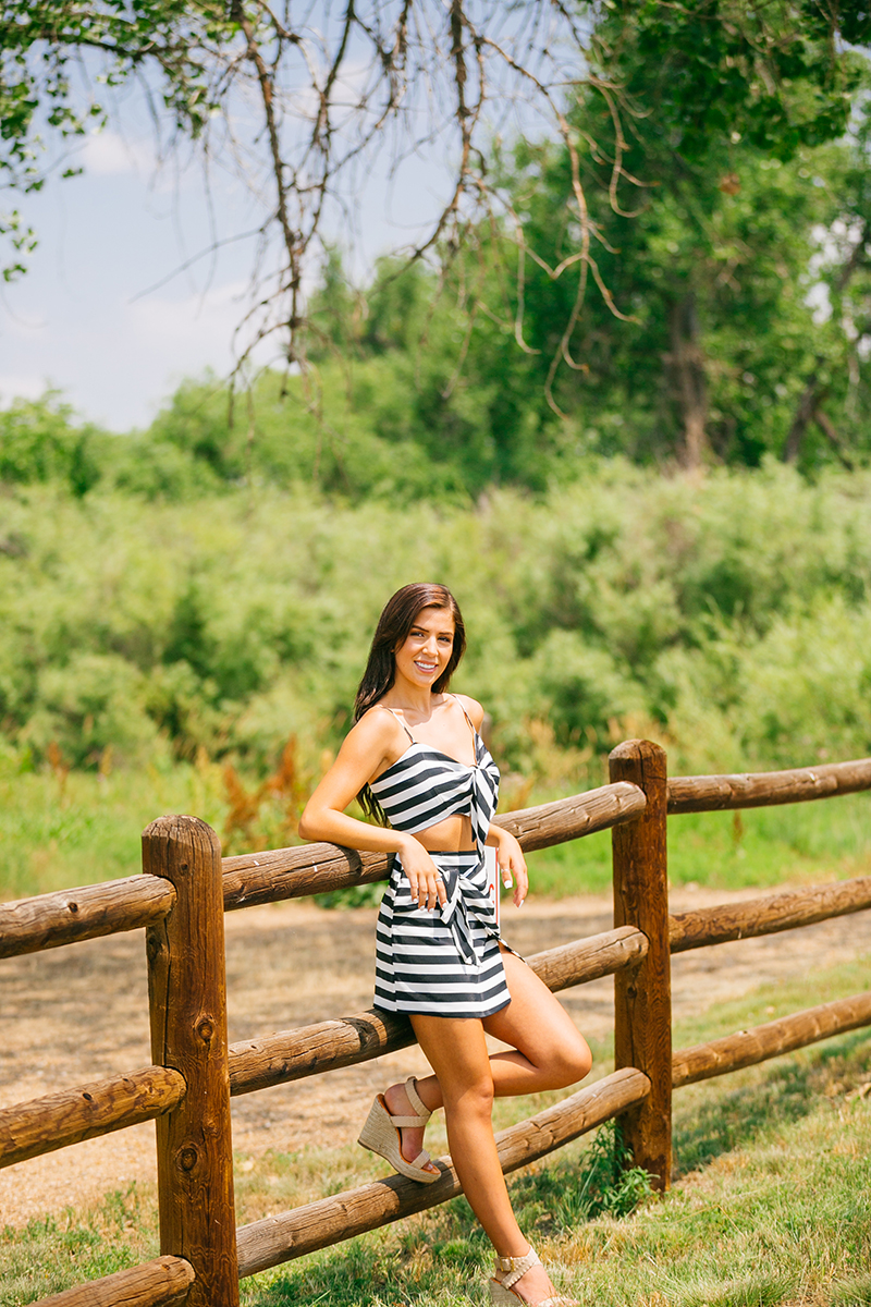 A beautiful young brunette poses against a wood fence in a lush green field wearing a striped top and skirt for a St Vrain fashion photography session near Denver, Colorado