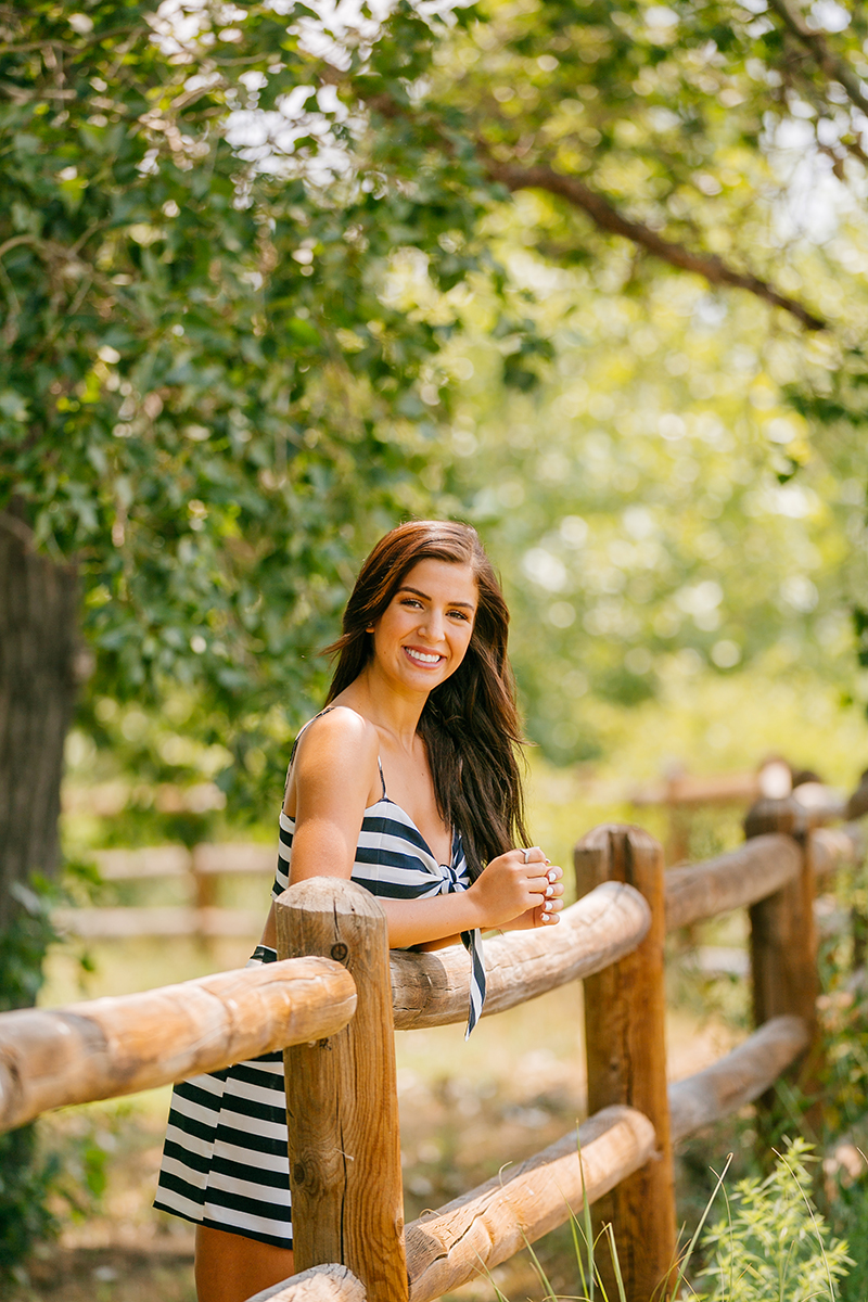 A beautiful young brunette leaning against a wood fence in a lush green field wearing a striped top and skirt for a St Vrain fashion photography session near Denver, Colorado