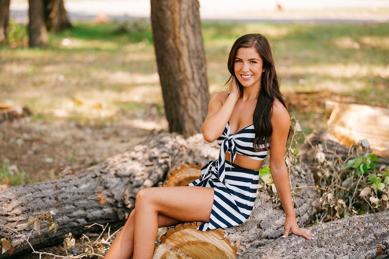 A beautiful young brunette sitting on a log surrounded by cut wood piles wearing a striped top and skirt for a St Vrain fashion photography session near Denver, Colorado