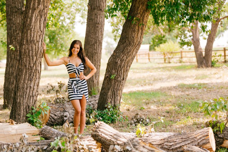 A beautiful young brunette leaning against a tree surrounded by cut wood piles wearing a striped top and skirt for a St Vrain fashion photography session near Denver, Colorado