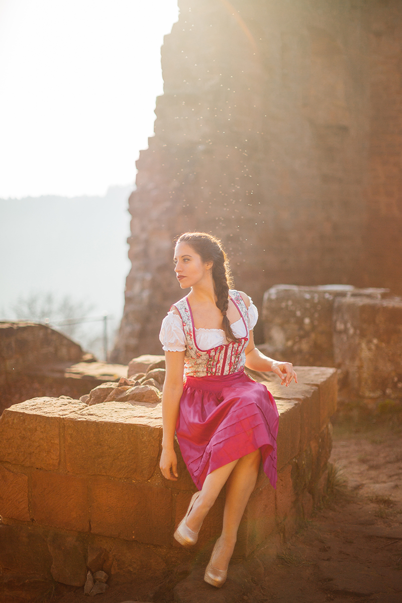 A beautiful young brunette woman posing inside a castle wearing a pink and white dirndl as the sun sets behind her for a Burg Hohenecken boudoir photography session near Kaiserslautern, Germany