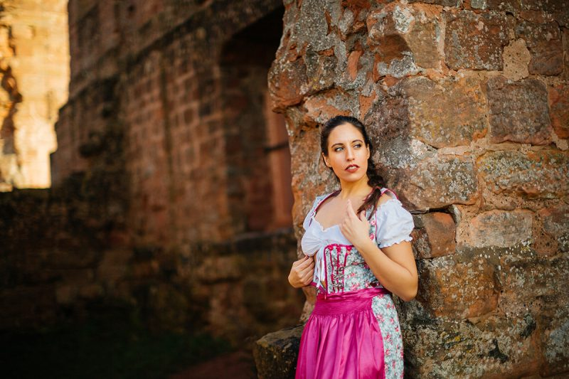 A beautiful young brunette woman leaning on a stone wall inside a castle wearing a pink and white dirndl as the sun sets behind her for a Burg Hohenecken boudoir photography session near Kaiserslautern, Germany