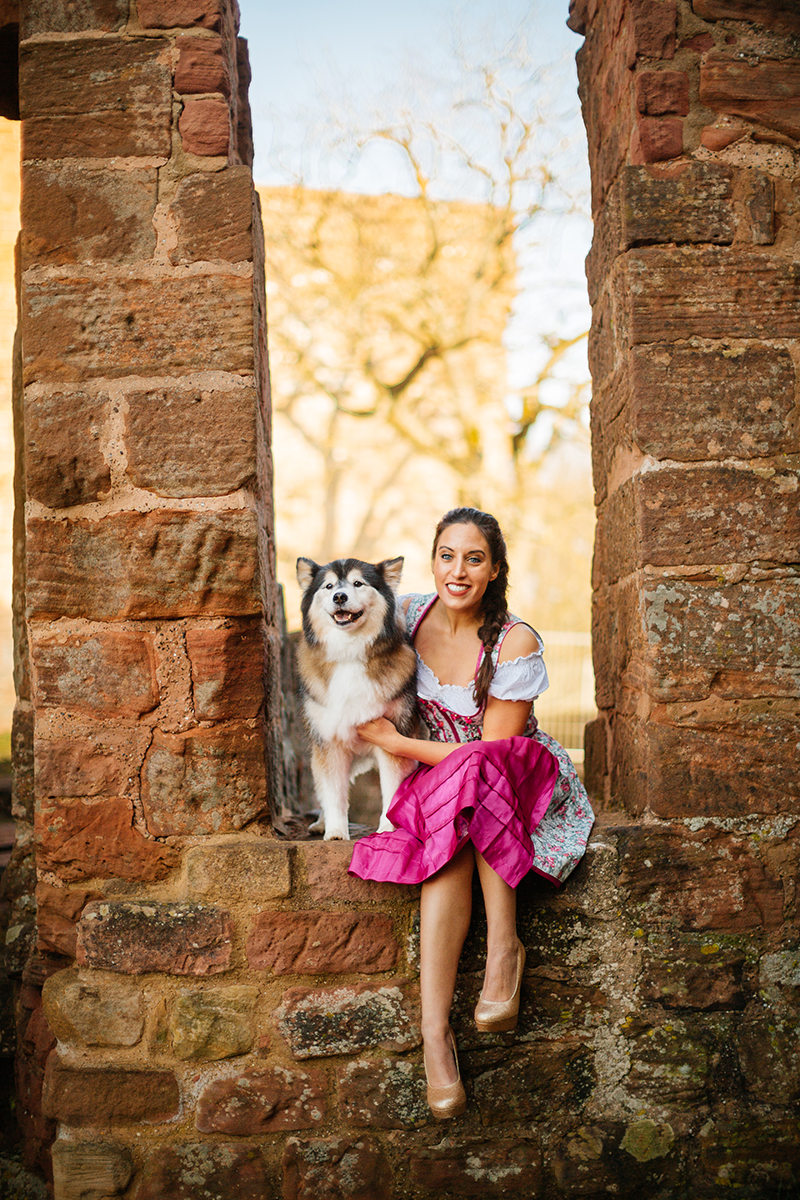 A beautiful young brunette woman sitting in a stone arch inside a castle wearing a pink and white dirndl as the sun sets behind her for a Burg Hohenecken boudoir photography session near Kaiserslautern, Germany