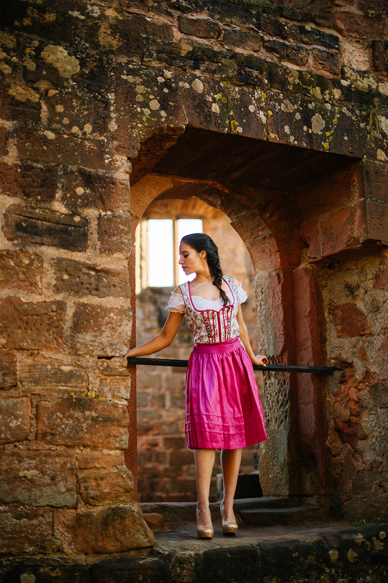 A beautiful young brunette woman posing in a stone arch inside a castle wearing a pink and white dirndl as the sun sets behind her for a Burg Hohenecken boudoir photography session near Kaiserslautern, Germany