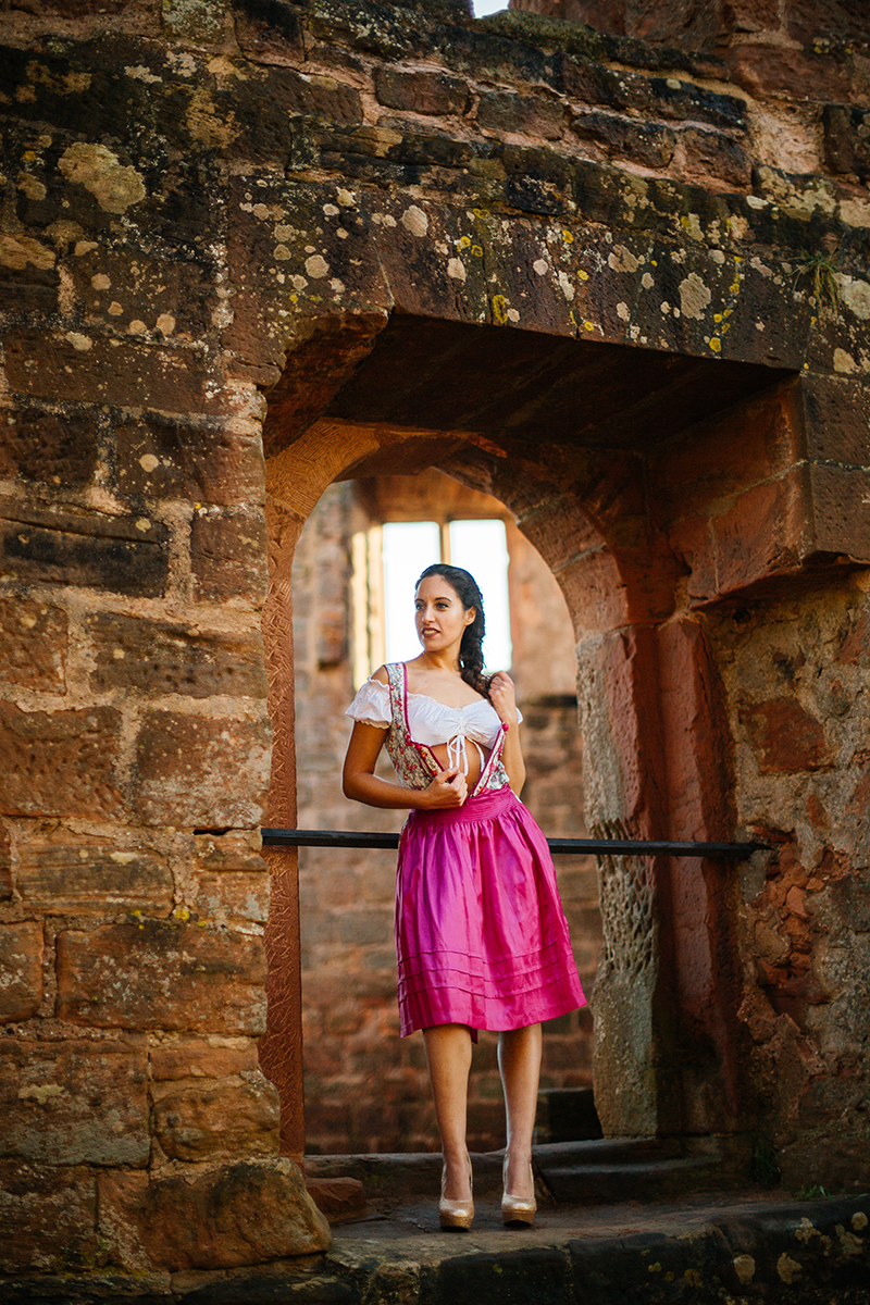 A beautiful young brunette woman undressing in a stone arch inside a castle wearing a pink and white dirndl as the sun sets behind her for a Burg Hohenecken boudoir photography session near Kaiserslautern, Germany