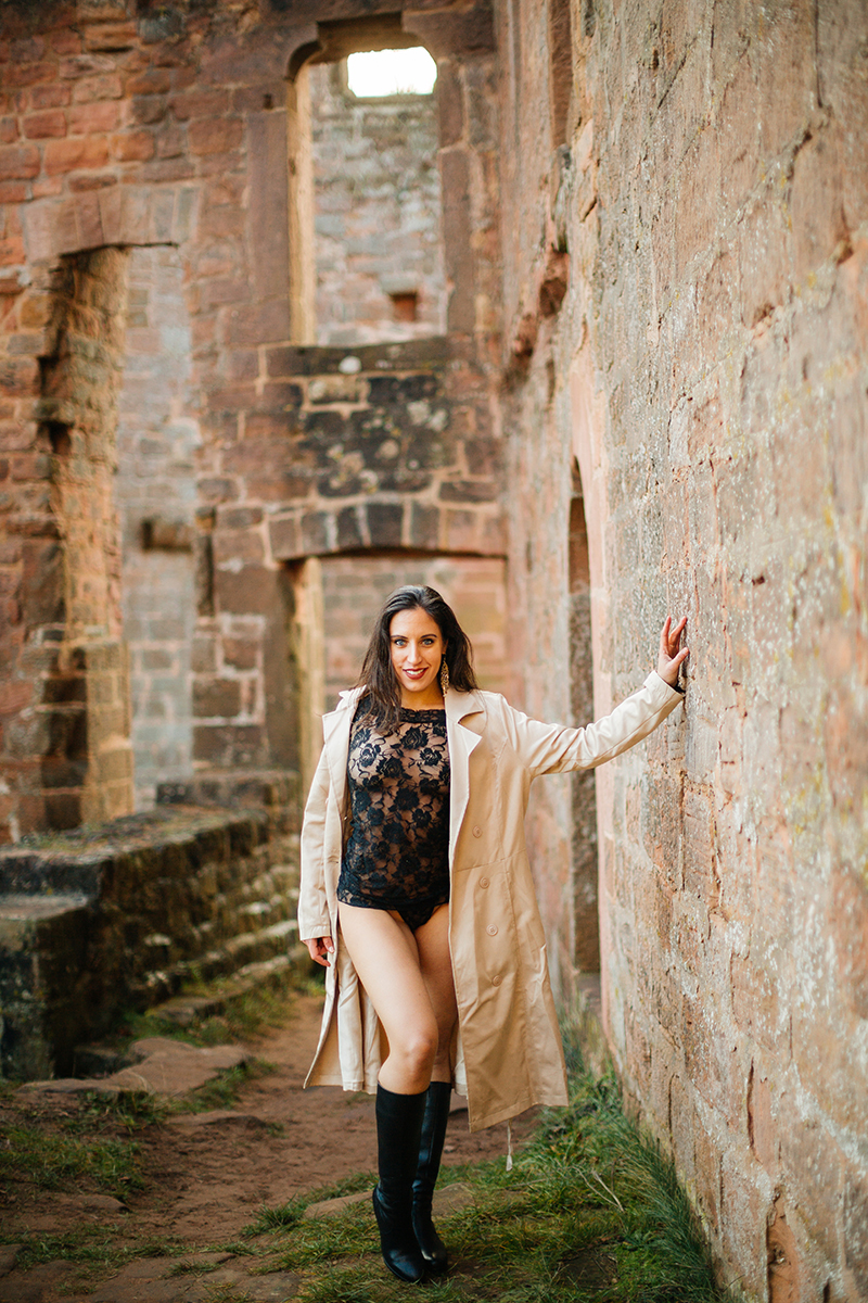 A beautiful young brunette woman leaning on a stone wall inside a castle wearing black lingerie and a tan overcoat as the sun sets behind her for a Burg Hohenecken boudoir photography session near Kaiserslautern, Germany