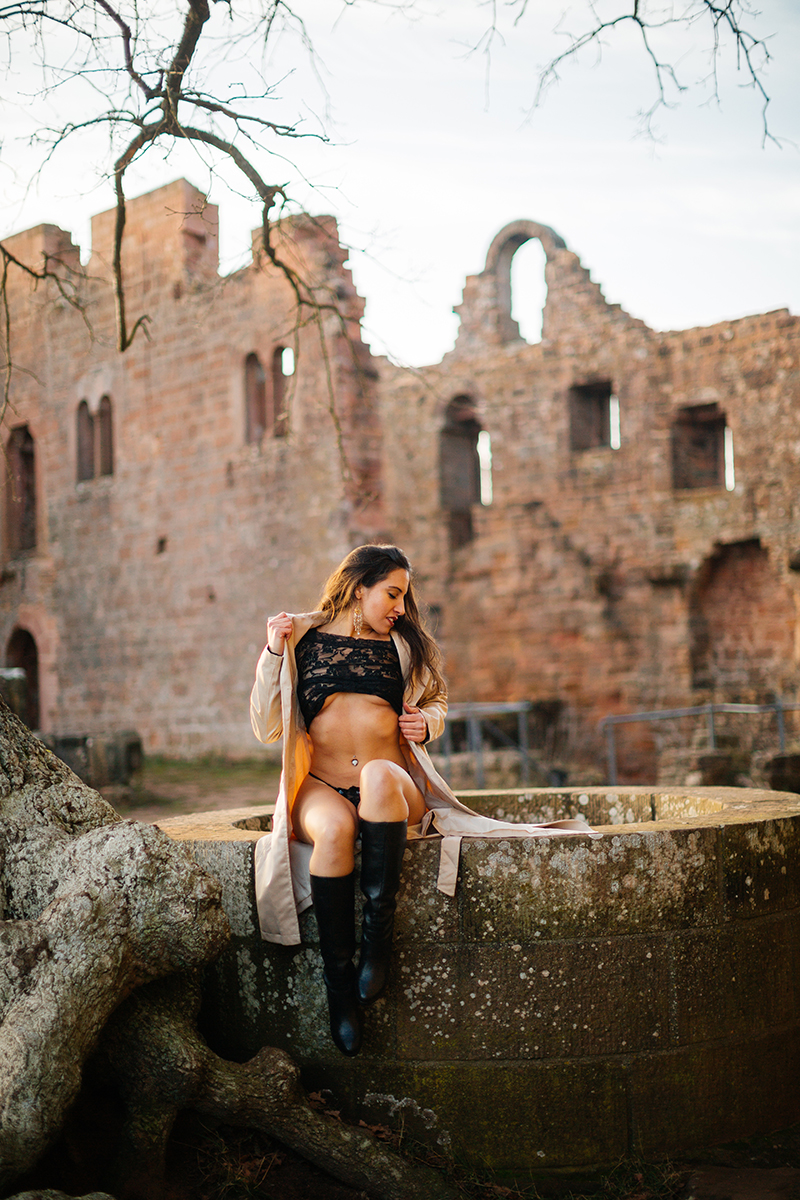 A beautiful young brunette woman sitting on a stone wall well a castle wearing black lingerie and a tan overcoat as the sun sets behind her for a Burg Hohenecken boudoir photography session near Kaiserslautern, Germany