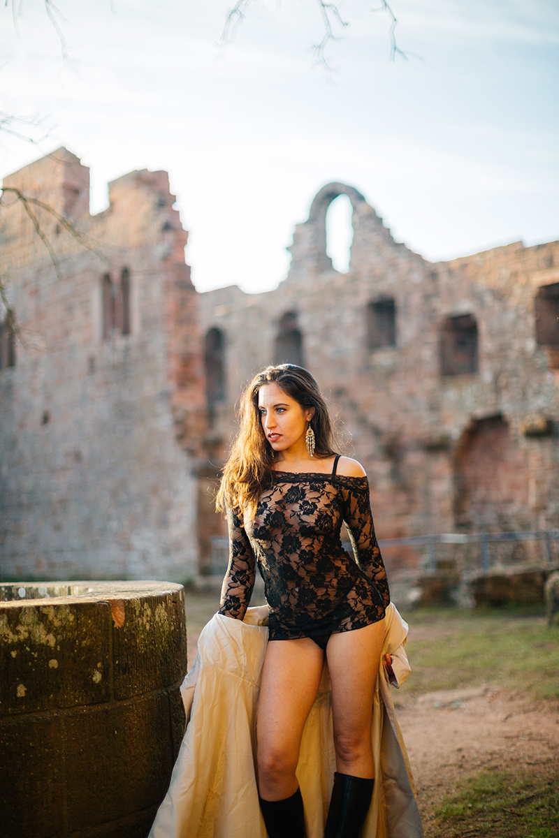 A beautiful young brunette woman leaning on a stone well a castle wearing black lingerie and a tan overcoat as the sun sets behind her for a Burg Hohenecken boudoir photography session near Kaiserslautern, Germany