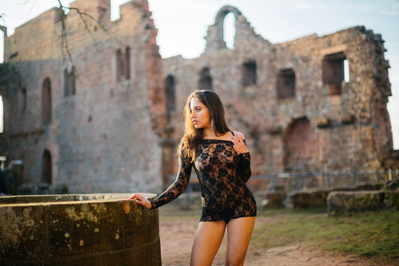 A beautiful young brunette woman leaning on a stone well a castle wearing black lingerie as the sun sets behind her for a Burg Hohenecken boudoir photography session near Kaiserslautern, Germany