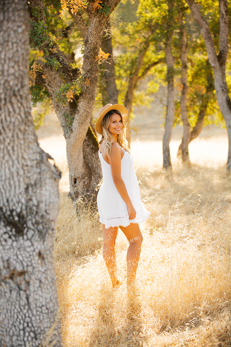A young beautiful blonde woman posing in a field with trees as the sun sets in a white dress and straw hat on a trail near Rancho Murieta for a Deer Creek Hills boudoir photography session