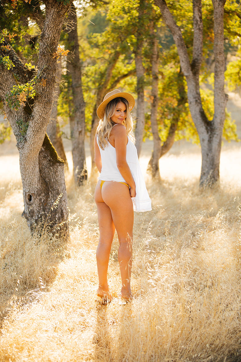 A young beautiful blonde woman posing in a field with trees as the sun sets pulling up her white dress showing her butt and straw hat on a trail near Rancho Murieta for a Deer Creek Hills boudoir photography session