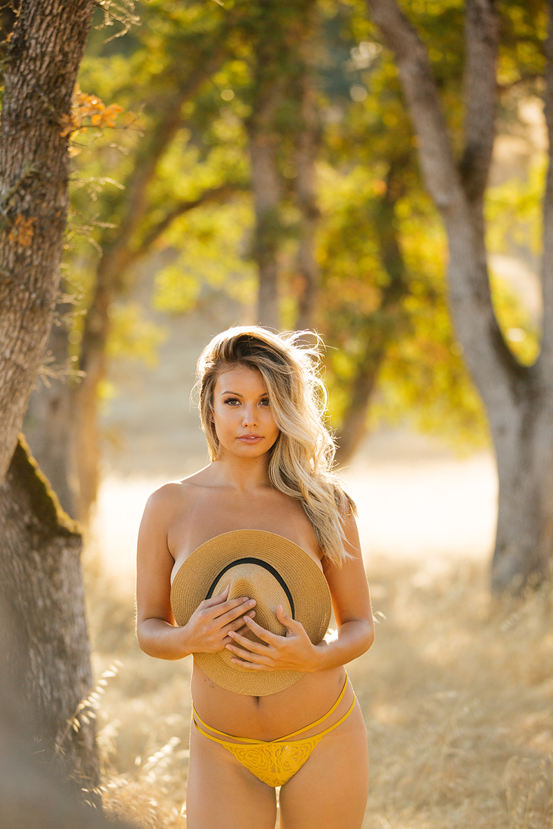 A young beautiful blonde woman posing topless in a field with trees as the sun sets with a straw hat covering her breasts on a trail near Rancho Murieta for a Deer Creek Hills boudoir photography session