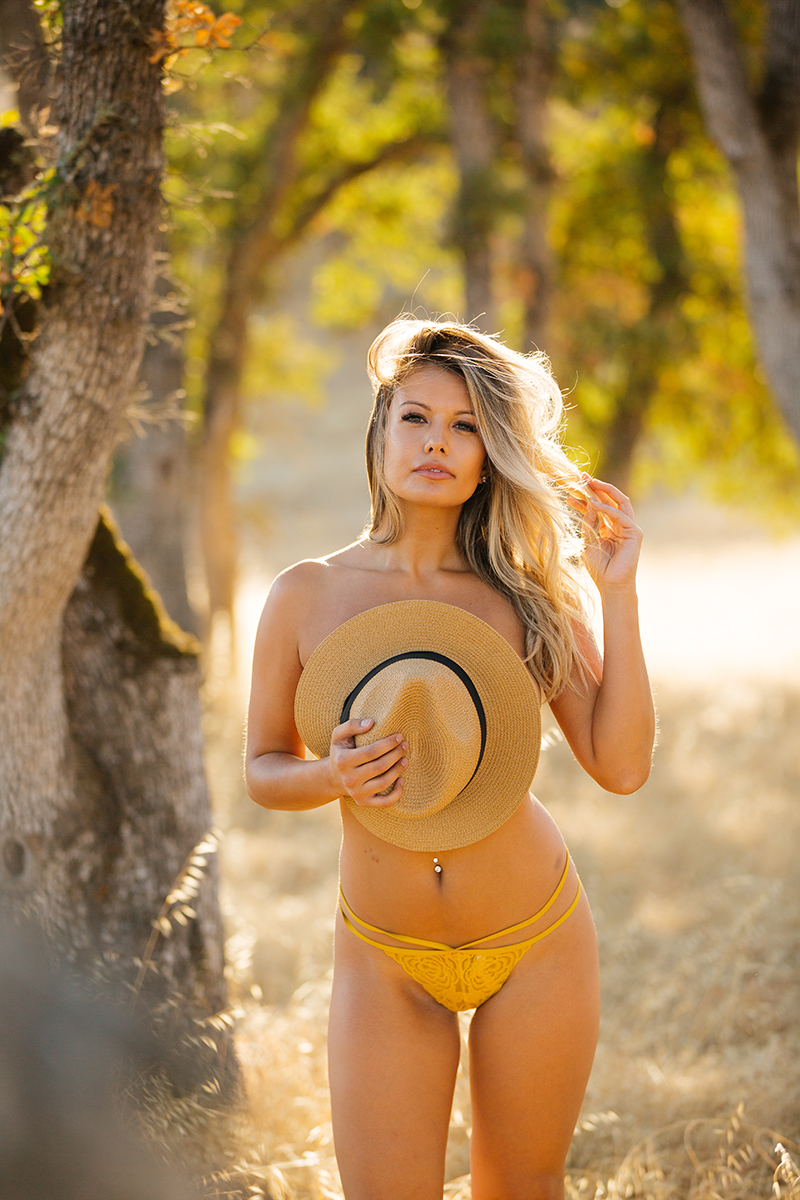 A young beautiful blonde woman posing topless in a field with trees as the sun sets with yellow underwear and a straw hat covering her breasts on a trail near Rancho Murieta for a Deer Creek Hills boudoir photography session